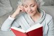 ältere, attraktive Frau genießt ein Buch - 26634039