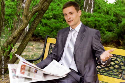 young businessman reading a newspaper in the park