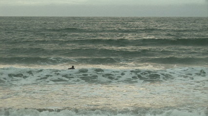 View of the sea with man going surfing