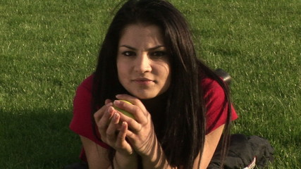 Captivating woman with an apple lying on the grass