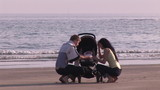 Young couple taking care of their baby on the beach