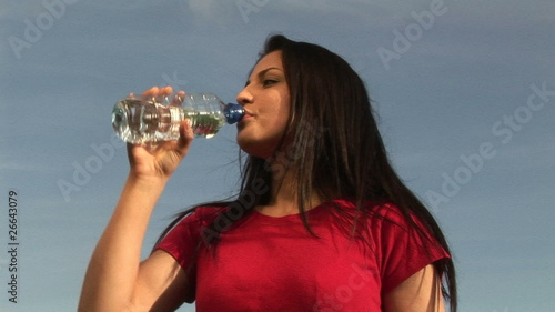 Below view of a woman drinking water with blue sky on background