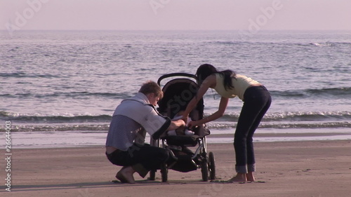 Young couple with baby on his pushchair walking by the ocean