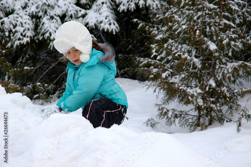 Little girl climbing on snow hill