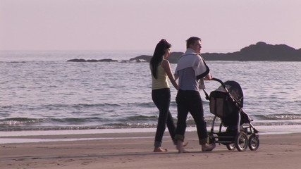 Happy couple walking on the beach with their baby on a stroller