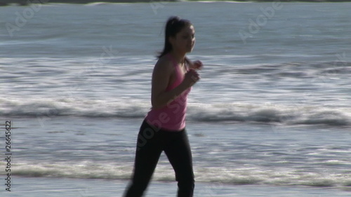 Attractive woman stretching and running on the beach