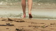Close up of a woman in the water standing back to the beach