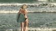 Rear view of a woman in the water with surfboard