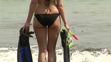 Rear view of woman on the beach with diving mask and flippers