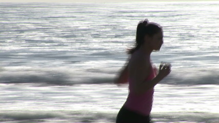 Captivating woman in sportswear running on the beach