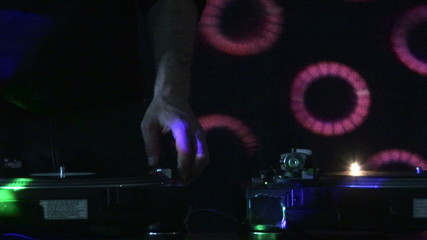 Front view of a Dj mixing in a discotheque