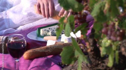 Close up of a woman picnicking surrounded by grapes