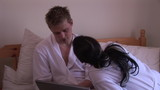 Young couple in bathrobe sitting with laptop in their bedroom