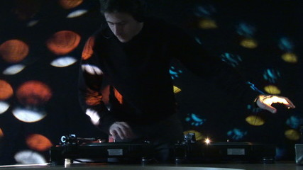 Dj performing with lighting effects in the background
