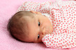 Portrait of a beautiful newborn baby girl on pink blanket