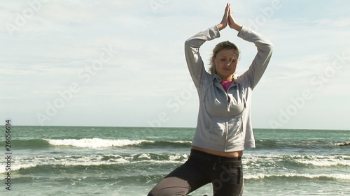 Woman practicing yoga on the beach