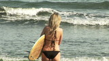 Beautiful woman on the beach ready to surf