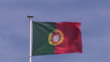 Portuguese flag in the wind with blue sky on background