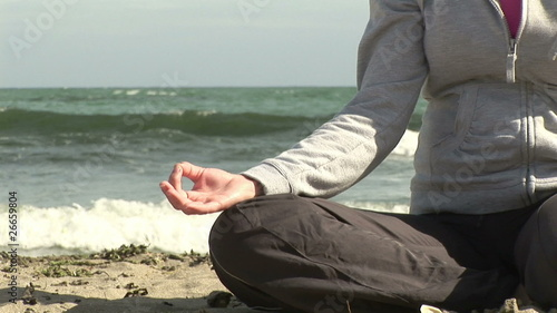 Close up of a woman doing yoga on the beach