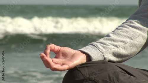 Close up of a woman doing yoga by the ocean
