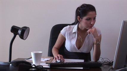 Captivating young businesswoman sitting at her desk