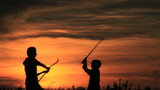 Boys battle sticks. Sunrise, a silhouette. Summer.