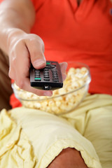 Young caucasian man's hand, remote control