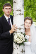 Happy smiling bride with groom outdoors next to birch tree