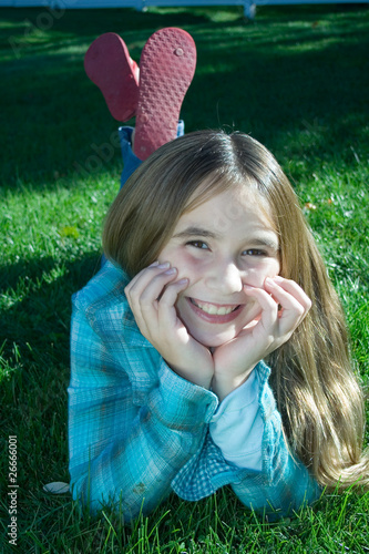 Smiling young girl laying in grass
