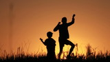 Boys play, a silhouette, sunrise