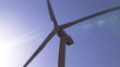Close up of a wind turbine turning against a sunny sky