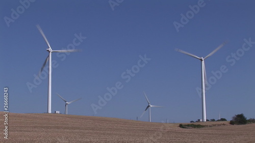 Below view of wind turbines in activity on a desert landscape