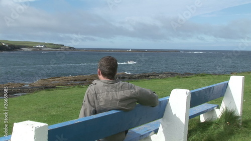Rear view of a man looking the bay sitting on a bench