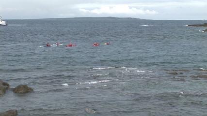 View from the beach of people doing some kayak in the sea