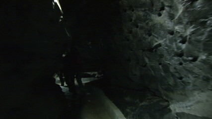 Rear view of explorers walking in a cave