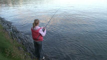 Rear view of a woman fishing a lake