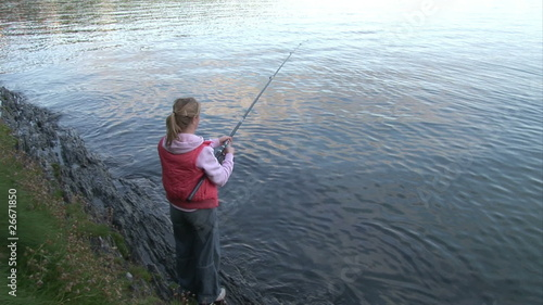Rear view of a woman fishing a lake