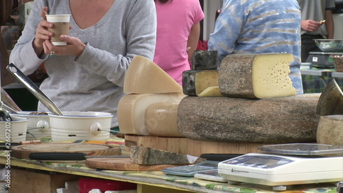 Close up of a female customer tasting melted cheese in a market