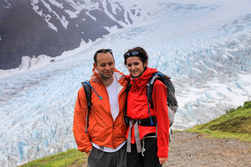 Young loving couple standing against Exit glacier, Alaska, USA