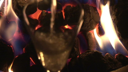 Close up of a fire in a chimney with flute of champagne