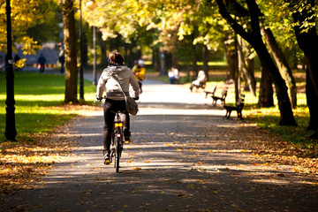 Woman on bicycle in park at fall