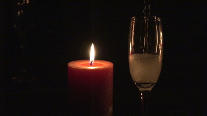 Candle and  flute of champagne in the dark