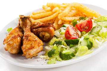 Grilled chicken drumsticks, chips and vegetables