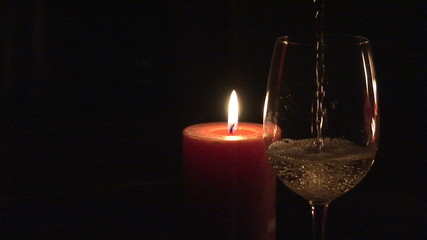 Candle with glass of white wine in the foreground in the dark
