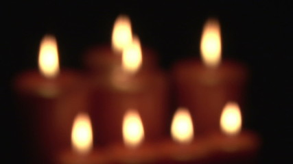 Eight blurred candles in the dark