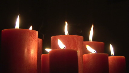 Close up of lit candles in the wind