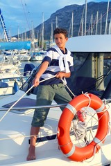 Boy teen sailor mooring boat rope in harbor