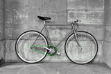 A fixed-gear bicycle in black and white with a green chain