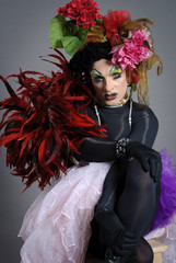 Drag Queen with flowers siting on chair