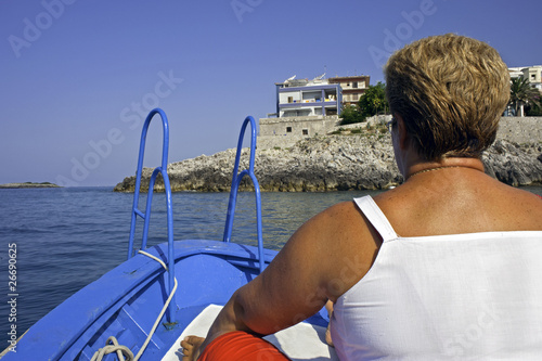 Coming back at home. A woman on a motorboat coastward